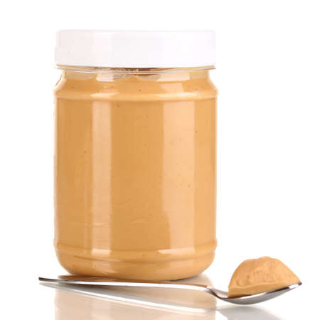 Delicious peanut butter in jar isolated on white photo