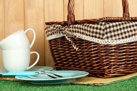 cups, plates and basket on grass on wooden background photo