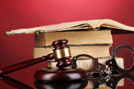 Gavel, handcuffs and book on law on red background photo