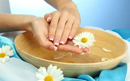 feminine hands: woman hands with wooden bowl of water with flowers, on blue background Stock Photo