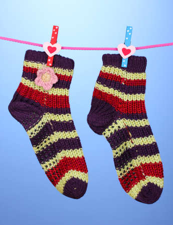 Pair of knit striped socks hanging to dry over blue background photo