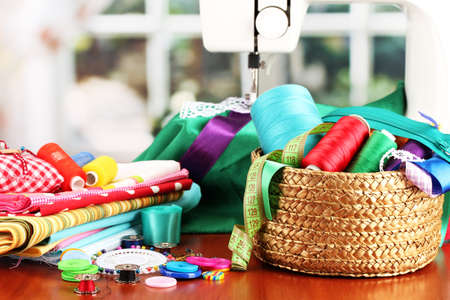 sewing box: sewing machine and fabric on bright background