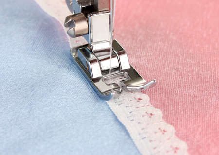 Closeup of sewing machine working part with  pink cloth photo