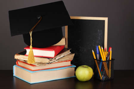 Books and magister cap against school board on wooden table on grey background photo