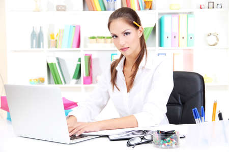 Young pretty business woman with notebook in office Stock Photo - 17051848