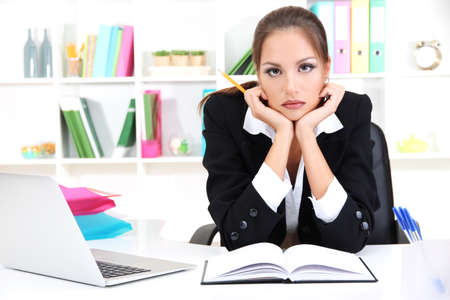 Thoughtful business woman with documents and notebook in office Stock Photo - 17051838