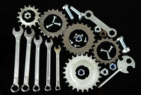 Machine gear, metal cogwheels, nuts and bolts isolated on black photo