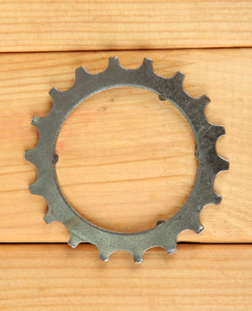 Metal cogwheel on wooden background photo