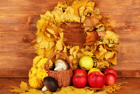 Autumnal composition with yellow leaves, apples and mushrooms on wooden background Stock Photo - 16791778
