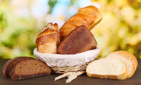 Fresh bread in basket on wooden table on natural background Stock Photo - 16787784