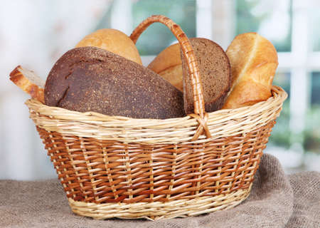Fresh bread in basket on wooden table on window background Stock Photo - 16791521