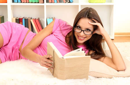 Young female relaxing on floor at home reading book Stock Photo - 17051814