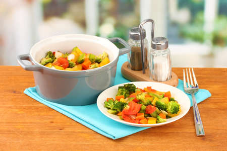 Vegetable stew in gray pot on wooden table on bright background photo