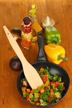 dripping pan: Sliced fresh vegetables in pan with spices and ingredients on wooden table