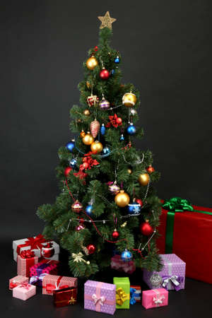 toygift: Decorated Christmas tree with gifts isolated on black