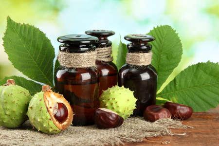 homeopatia: frascos de medicinas con casta�as y hojas sobre fondo verde
