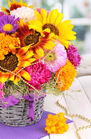 Beautiful bouquet of bright flowers on wooden table on window background photo