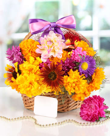Beautiful bouquet of bright flowers in basket with paper note on white table on window background photo