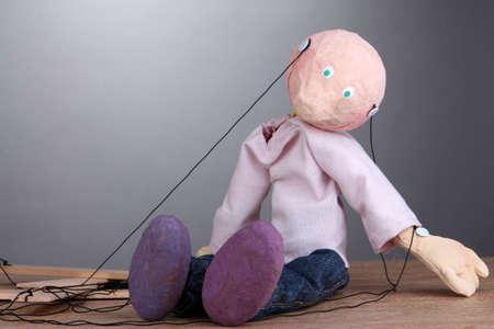 marioneta de madera: Mu�eco de madera sentado sobre fondo gris Foto de archivo