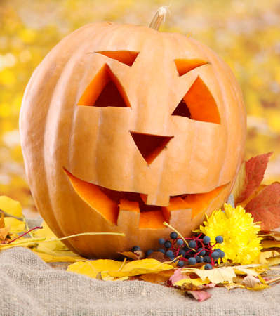 halloween pumpkin and autumn leaves, on yellow background Stock Photo - 16739600
