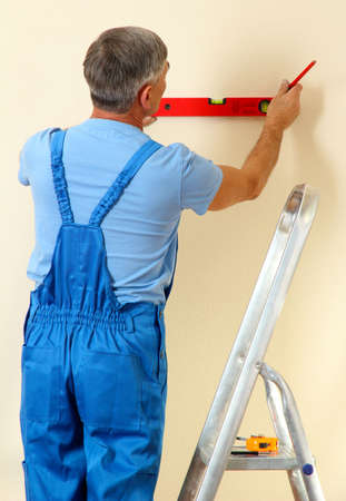 Builder measuring wall in room close-up photo