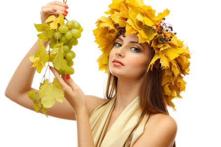 beautiful young woman with yellow autumn wreath and grapes, isolated on white photo