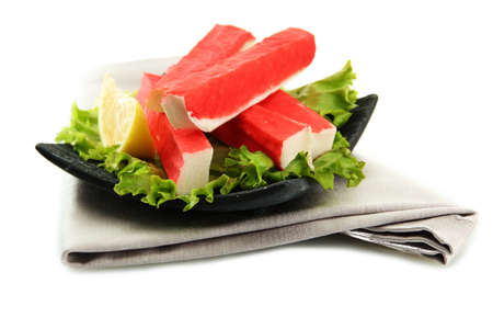 crabmeat: Crab sticks with lettuce leaves and lemon on plate isolated on white