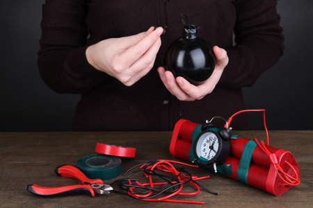 Human makes timebomb on wooden table on black background Stock Photo - 16739657