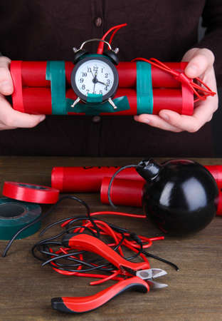 timebomb: Human makes timebomb on wooden table on black background