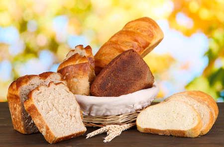 canasta de pan: Pan fresco en cesta en la mesa de madera sobre fondo natural