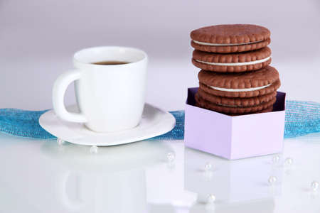 Chocolate cookies with creamy layer and cup of coffe on purple background photo