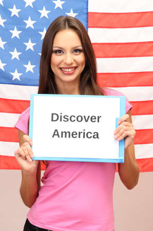 Young woman young woman holding tablet on background of American flag photo