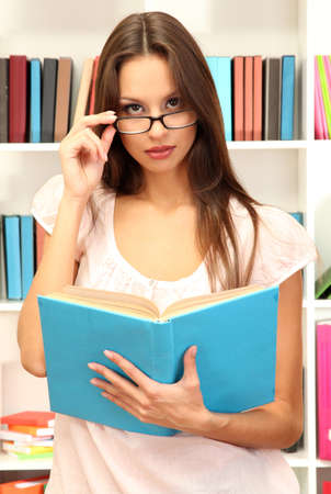 Young attractive female student reads book in library photo
