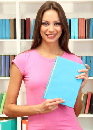Young attractive female student with book in library photo