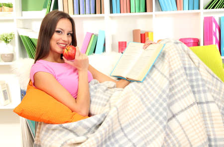 Portrait of female eating apple and reading book while lying on couch Stock Photo - 17281792