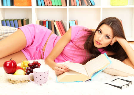 Young female relaxing on floor at home reading book Stock Photo - 17281793