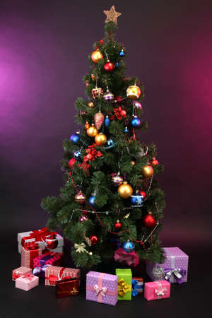 Decorated Christmas tree with gifts on dark color background photo