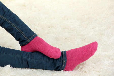 Female legs in colorful socks on  white carpet background Stock Photo - 16739876