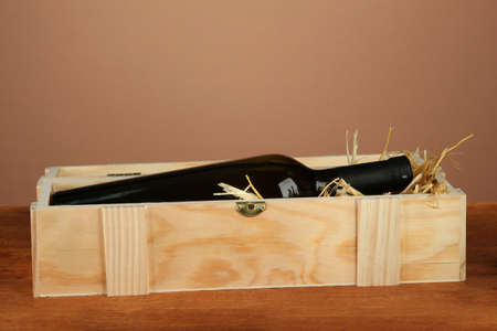 Wine bottle in wooden box on wooden table on brown background Stock Photo - 16739754