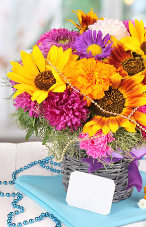 Beautiful bouquet of bright flowers with paper note close-up on wooden table on window background photo