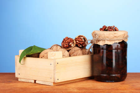 jam-jar of walnuts and  wooden box on blue  background photo