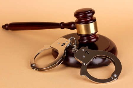 Gavel and handcuffs on beige background photo