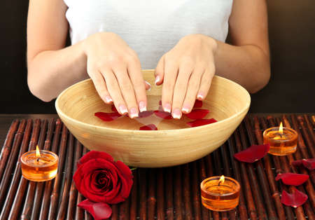 woman hands with wooden bowl of water with petals, on brown background photo