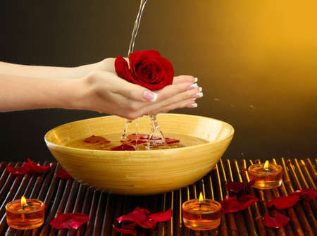 woman hands with wooden bowl of water with petals, on brown background Stock Photo - 16765229