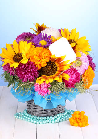 ronantic: Beautiful bouquet of bright flowers with paper note on wooden table on blue background