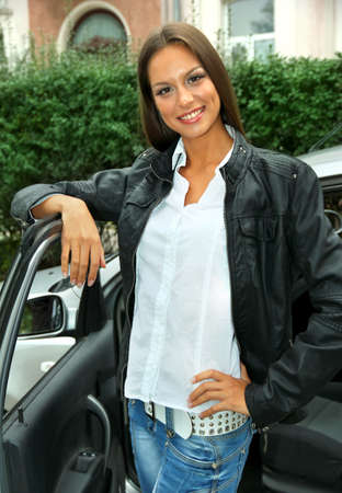 beautiful young woman standing near car photo