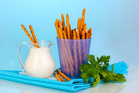 Tasty crispy sticks in purple plastic cup on blue background photo