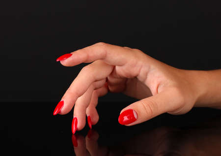 Beautiful female hands with red nails isolated on black Stock Photo - 16772380