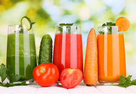 Fresh vegetable juices on wooden table, on green background Stock Photo - 16772394