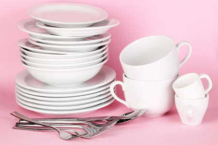 clean kitchen: Clean white dishes on pink background